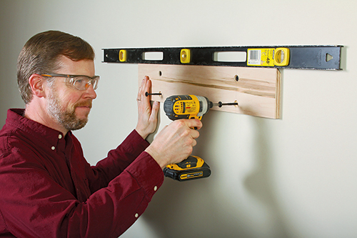 Level and fasten the wall cleats to two wall studs, with four heavy-duty screws
